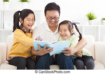 happy father read the book to children