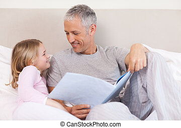 Happy father reading a story to his daughter