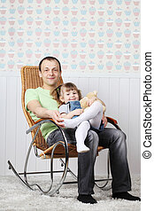 Happy father sits with little daughter in rocking chair