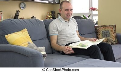 Happy father sitting on sofa invite his toddler daughter to read book together.