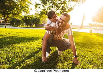 Happy father spending time with his little son at the park
