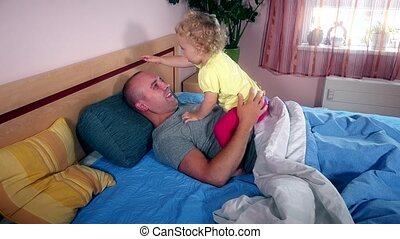 Happy father spent time with his daughter on bed in bedroom....