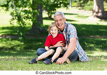 Happy father using tablet pc with his son
