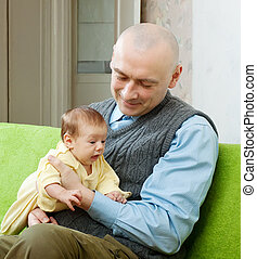 Happy father with 2 month baby in home interior