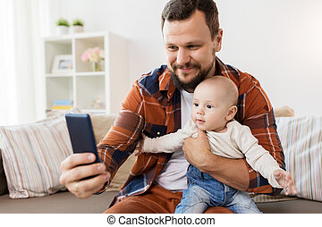happy father with baby boy taking selfie at home