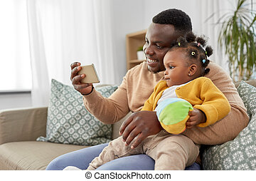 happy father with baby taking selfie at home