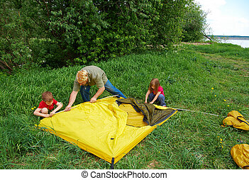 Father with children installing their tent