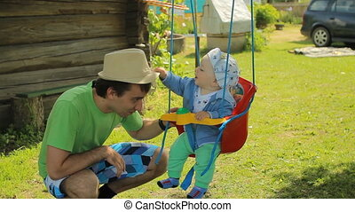 Happy father with his cute baby boy playing with swing