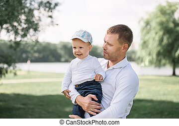 happy father with his little son standing in a Sunny Park.