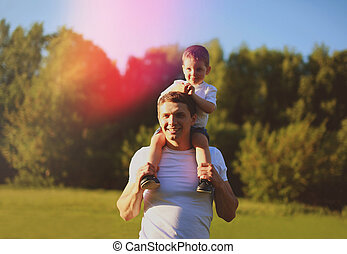 Happy father with son having fun outdoors, sunny summer day, war