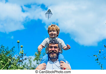Happy father with son playing with toy plane. Dream to be pilot. Father with child have fun joy on nature at day time. Boy with toy aeroplane sitting on fathers shoulders at park. Family happy travel