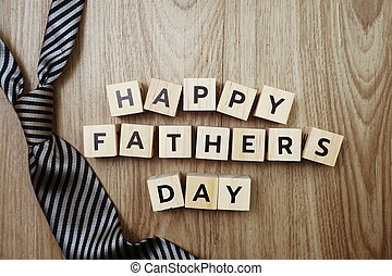 Happy Father's Day alphabet letters with necktie on wooden background