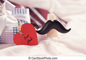 Happy fathers day concept. Gift box with red heart tag, purple flower, mustache and red tie on white cheesecloth background.