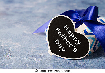 Happy Fathers Day concept. Gift box with ribbon. Heart shaped chalkboard on blue background.