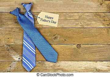 Happy Fathers Day gift tag with blue neckties on rustic wood background