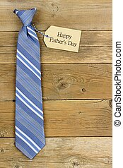 Happy Fathers Day gift tag with blue striped necktie on rustic wood background
