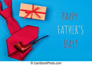 Happy Father's day greeting card with composition of red neck tie, gift box with red ribbon and smoking tobacco pipe on blue cyan background with inscription Happy Father's day.
