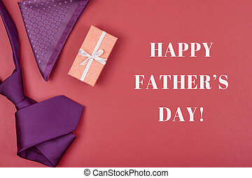 Happy Father's day greeting card with composition of violet neck tie, gift box with white ribbon, pocket square on red brown background with inscription Happy Father's day.