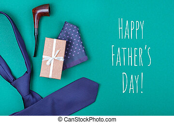 Happy Father's day greeting card with composition of violet neck tie, gift box with white ribbon, pocket square and smoking tobacco pipe on emerald blue-green background with inscription Happy Father's day.
