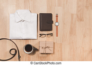 Happy Father's Day inscription with hand watch, shirt, coffee cup, notebook and cupcake on wooden background floor backround.