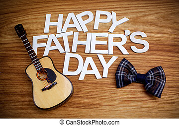 Happy Fathers Day letters with guitar on wooden background. Top view