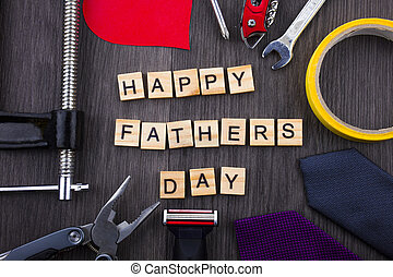 Happy Fathers Day message on a wooden background with frame of tools and ties.