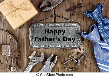 Happy Fathers Day message on metal sign with frame of tools, gifts and ties on a wooden background