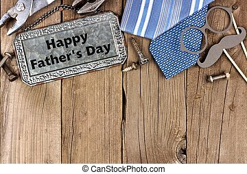Happy Fathers Day message on metal sign with top border of tools and ties on a wooden background