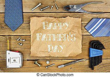Happy Fathers Day message on rustic paper with frame of tools and ties on a wooden background