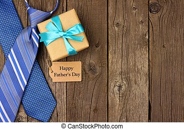 Happy Fathers Day side border with gift tag, gift and ties on rustic wood
