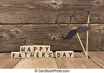 Happy Fathers Day wooden blocks with mustache and glasses against a rustic wooden background