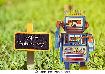 happy fathers day word. Toy robot with sign on green grass.