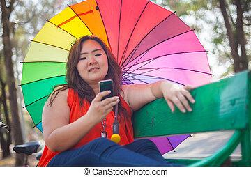 Happy fatty woman using mobile phone - Happy fatty asian...