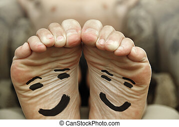 Funny image of a pair of bare male feet with happy smiley face drawn on bottom