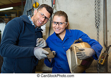 happy female apprentice welder at work in the plant