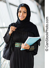 female arabian college student holding a book