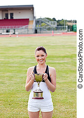 Happy female athlete holding a trophy