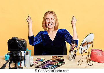 Happy female beauty fashion blogger clenching fists, celebrating success