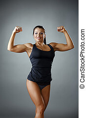Happy female bodybuilder showing her biceps