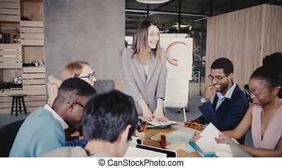Happy female boss leading office team meeting. Multiethnic...