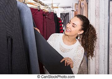 Happy female brunette choosing new trousers