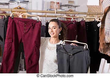 Happy female brunette choosing trousers