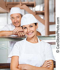 Happy Female Butcher With Colleague At Butchery