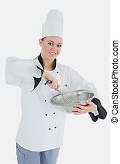 Happy female chef holding wire whisk and mixing bowl
