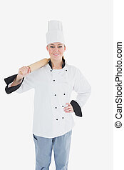Happy female chef in uniform holding rolling pin