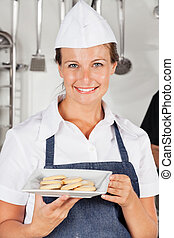 Happy Female Chef Presenting Cookies
