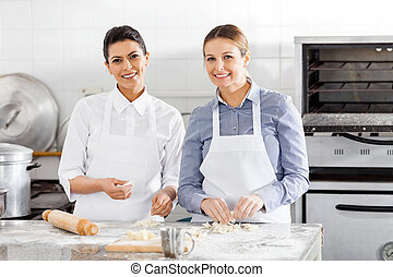 Happy Female Chefs Preparing Pasta At Counter
