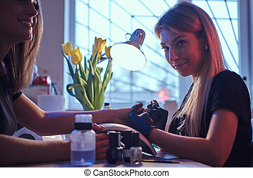 Happy female client and beautician master in the beauty salon.