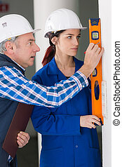 happy female constructor showing assistant measuring the wall indoors