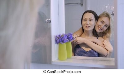Happy female couple embracing near the mirror
